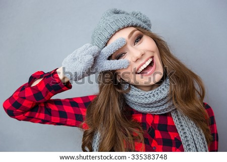 Portrait of a funny laughing woman showing two fingers sign over gray background - stock photo