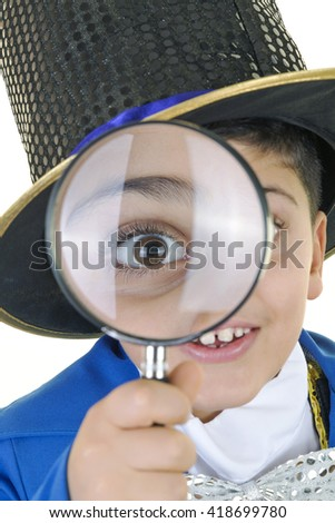 Portrait of a funny little boy in mad hatter costume is looking from magnifying glass and getting surprised and smiling to the camera against isolated white background.