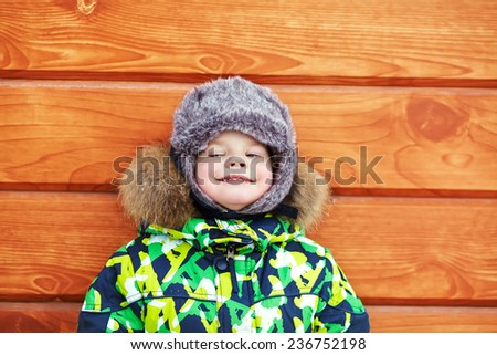 portrait of a funny little boy on a walk in the winter. child outdoors - stock photo
