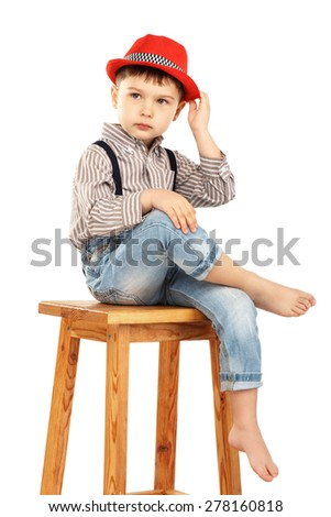 Portrait of a funny little boy sitting on a high stool in a red hat isolated on white background - stock photo