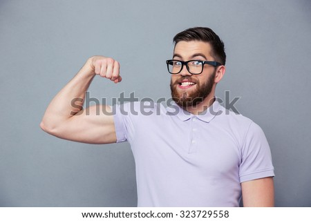 Portrait of a funny man in glasses showing his muscles over gray background - stock photo