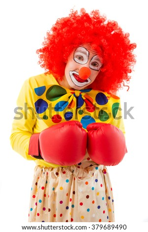 Portrait of a funny playful clown in red wig and boxing gloves making faces and looking at camera, isolated on a white background