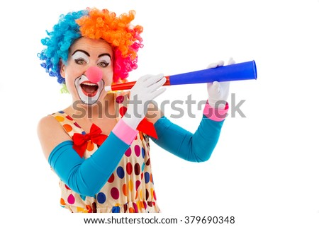 Portrait of a funny playful female clown in colorful wig blowing horn, looking at camera and smiling, isolated on a white background - stock photo