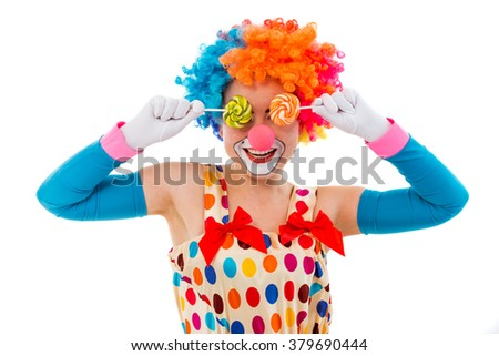 Portrait of a funny playful female clown in colorful wig covering eyes with lollipops and smiling, isolated on a white background - stock photo