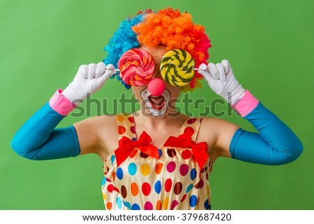 Portrait of a funny playful female clown in colorful wig covering her eyes with lollipops, standing on a green background - stock photo