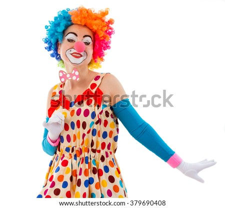 Portrait of a funny playful female clown in colorful wig holding a pink bow tie on stick and looking at camera, isolated on a white background - stock photo