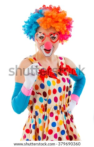 Portrait of a funny playful female clown in colorful wig holding heart glasses on stick and looking at camera, isolated on a white background - stock photo