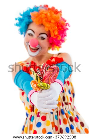Portrait of a funny playful female clown in colorful wig holding lollipops, looking at camera and smiling, isolated on a white background, focus on hands - stock photo