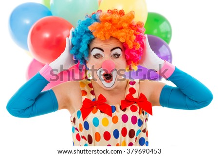 Portrait of a funny playful female clown in colorful wig keeping hands on head and showing emotions, in the background balloons, isolated on a white