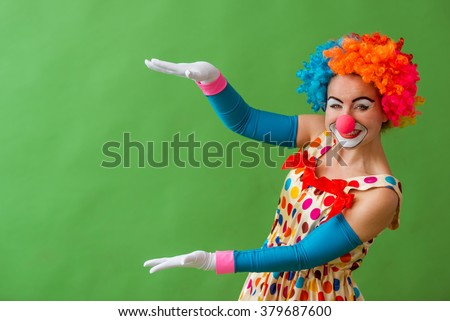 Portrait of a funny playful female clown in colorful wig showing, looking at camera and smiling, standing on a green background - stock photo