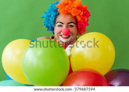 Portrait of a funny playful female clown in colorful wig with balloons, looking at camera and smiling, standing on a green background - stock photo
