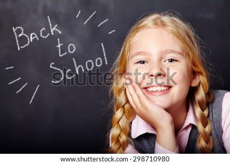 Portrait of a funny schoolgirl on blackboard background. School and education - stock photo