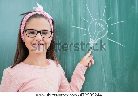 Portrait of a funny schoolgirl on blackboard background. School and education. concept idea