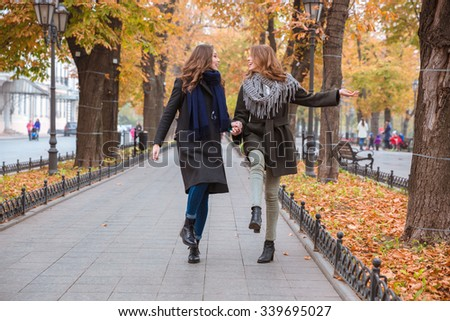 Portrait of a funny two girlfriends walking in autumn park