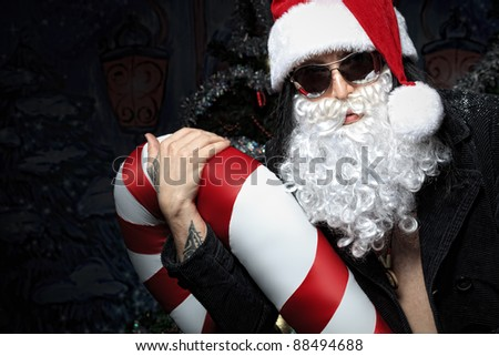 Portrait of a funny young man in Santa Claus hat and beard. Christmas. - stock photo