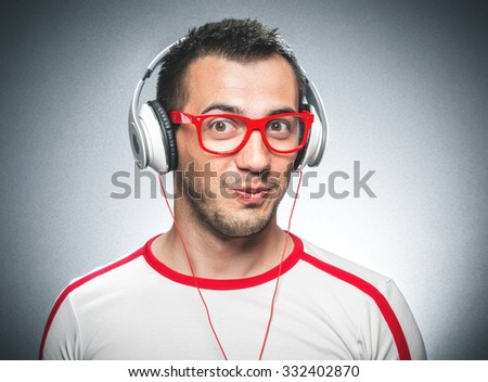 Portrait of a funny young man make a comic face and listening music with headphones against a dark gray background - stock photo