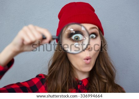 Portrait of a funny young woman looking at the camera through magnifying glass over gray background - stock photo