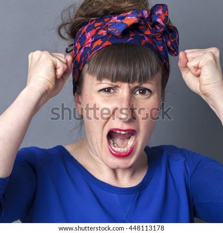 portrait of a furious childish woman with bangs and a fifties scarf as retro hairstyle shouting with fists up, being enraged and exasperated over grey background