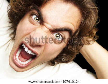 portrait of a furious young man shouting against a black background - stock photo
