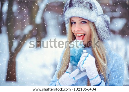 portrait of a gentle glamorous woman in a winter hat with a winter drink In cold tones, snow falls, artistic toning. Concept of rest and fun in winter.