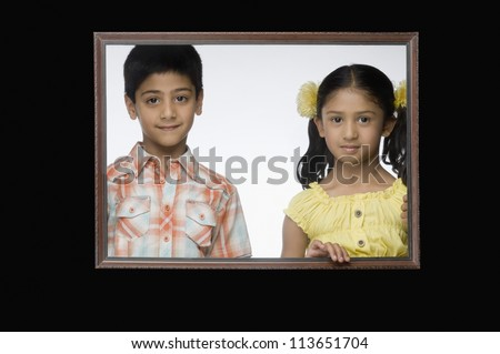 Portrait of a girl and a boy in a picture frame - stock photo