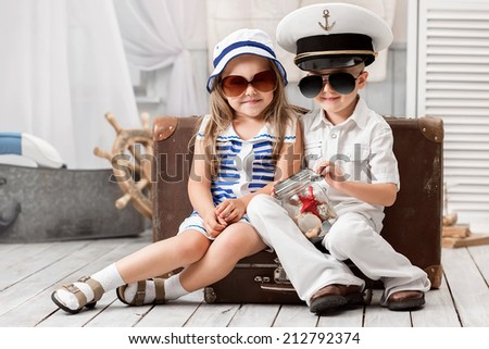 Portrait of a girl and a boy sailors playing in his room - stock photo