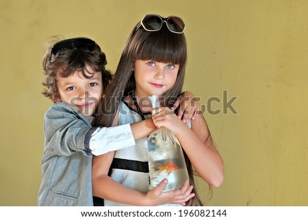 Portrait of a girl and boy with a goldfish - stock photo