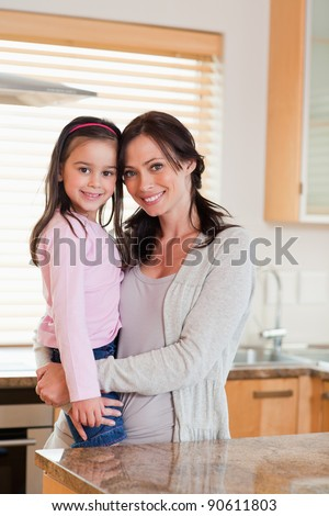 Portrait of a girl and her mother in a kitchen - stock photo