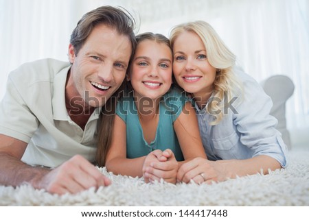 Portrait of a girl and her parents lying on a carpet in the living room - stock photo