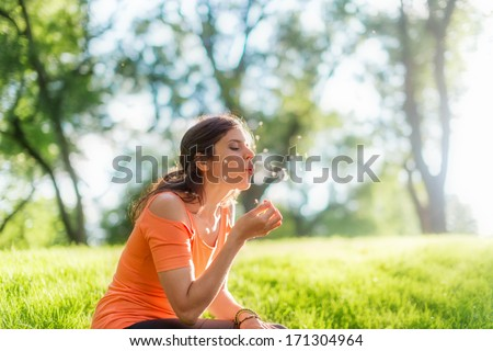 Portrait of a girl blowing a dandelion at sunset - stock photo