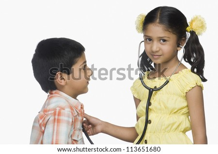 Portrait of a girl examining a boy with a stethoscope - stock photo