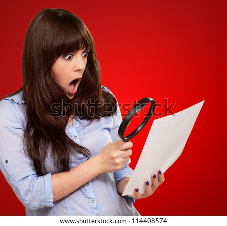 Portrait Of A Girl Holding A Magnifying Glass And Paper On Red Background - stock photo