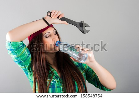 portrait of a girl holding a wrench - stock photo