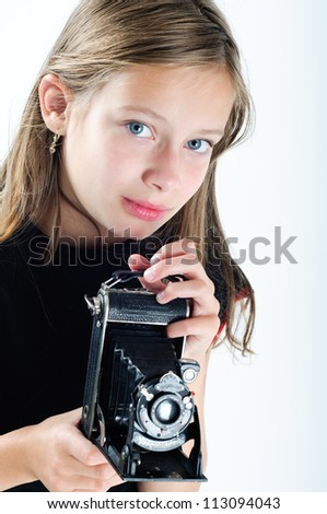 portrait of a girl holding an old camera