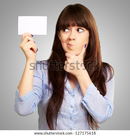 Portrait Of A Girl Holding And Making A Pout On Grey Background - stock photo