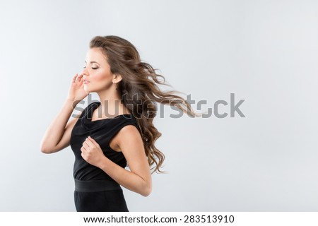 Portrait of a girl in a black dress. Hair wind. - stock photo