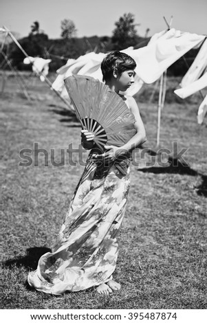 portrait of a girl in a field with a fan