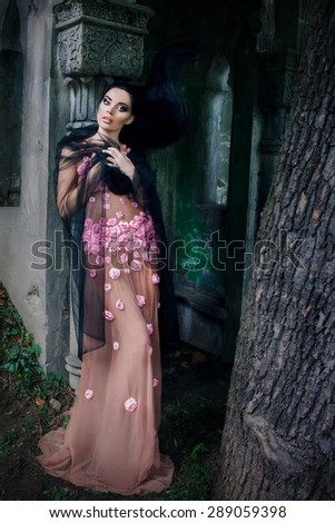 portrait of a girl in a pink dress and a black veil near the tomb in the cemetery