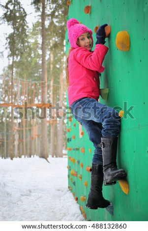 Portrait of a girl in a pink jacket and hat on a green wall for climbers in the winter