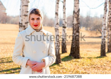 portrait of a girl in a white coat on the background of birch trees - stock photo