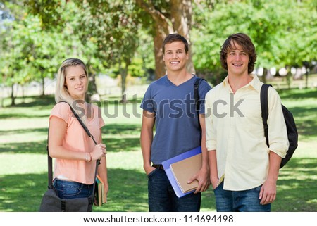 Portrait of a girl in front of two students in a park