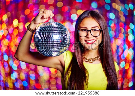 Portrait of a girl in glasses holding disco ball - stock photo