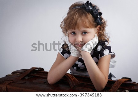 Portrait of a girl in gloves with a suitcase