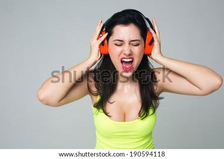 Portrait of a girl in headphones. She screams - stock photo