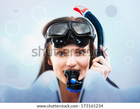 Portrait of a girl in snorkeling gear on blue background with some bubbles - stock photo