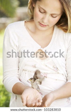 Portrait of a girl in the garden, holding a bird in her hands and smiling. - stock photo