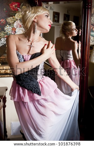 portrait of a girl in the interior on the background of pictures and mirrors - stock photo