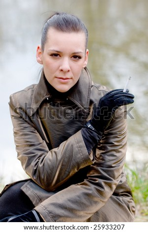 portrait of a girl in the park with cigar - stock photo