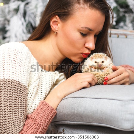 Portrait of a girl in white clothes with a little hedgehog together over light christmas background