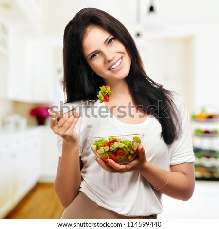 Portrait of a girl looking positive and holding a bawl with salad - stock photo